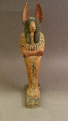 A statuette of Anubis, jackal-headed god of the dead in the form of a mummy. It is a historical replica and is made from wood and painted plaster. It is made in the style of ancient Egypt and probably related to the XIX dynasty from the New Kingdom (1550-1069 BCE). © Australian Museum