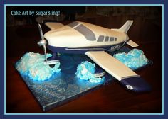 I made this airplane cake by sculpting the cake into the general shape and covering it with fondant.  I added fondant accents and gumpaste propeller, tail and back wings. The front wings are made from foam core board for support, and covered in fondant.  The clouds are cake frosted in buttercream.This custom cake was created by SugarBling! - a cake boutique located in Kansas City, Missouri.