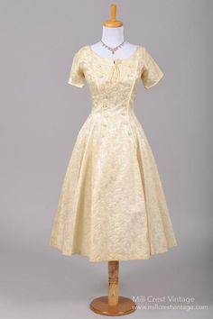 Designed in the 50's, this stunning vintage wedding dress is done in a champagne toned weighted silk jacquard over a linen lining in the bodice. We have pair...