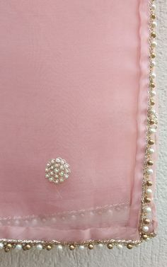 Featuring this beautiful Light Pink saree in Organza base with hand embroidered pearl work bootis all over. It is paired with a Plain wine colour Dupion blouse with Pearl Work on Front, back and sleeves. Note- You can select Blouse stitching options from above. Kindly provide the blouse measurements, if required, in t