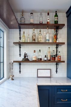 Open cabinets -- or just shelving -- is a surprise in a kitchen. Usually we're trying to hide stuff! Here, simple tile walls and classic Carrera marble tile countertops create the perfect setup for these rustic shelves used to hold liquor bottles and wine. Any other materials or colors might have made the space feel too busy.