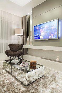 Sala com poltrona diferente e mesa de centro feita com espelhos