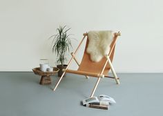 Ovis hanging chair is a reinterpretation of a classic sling chair while using unexpected material combinations to celebrate each material's innate quality. A metal and whitened maple frame supports a leather sling. Felt Head pillow is made with 90% wool content. Each chair is hand-ass