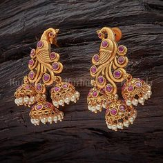 Peacock design antique earrings studded with synthetic white and ruby stones, made of copper alloy, plated with gold polish Indian Jewelry Earrings, Gold Jhumka Earrings, Jewelry Design Earrings, Gold Earrings Designs, Gold Jewellery Design, Silver Drop Earrings, Antique Earrings, Gold Jewelry, Earring Studs