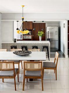 """O padrão gráfico do balcão, com ladrilhos da Colormix, faz um conjunto descolado com o pendente amarelo (Lustres Irie), que reúne várias luminárias. Esse é o espírito da cozinha assinada pelo arquiteto Thiago Papadopoli. O projeto buscou a praticidade máxima, como desejavam os proprietários do apartamento. Entre os revestimentos cerâmicos, fáceis de limpar, a madeira aparece para trazer calor. """"Escolhi acabamentos neutros para que a estrela do espaço fosse a marcenaria"""", explica. Centro de…"""