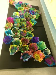 "Preschool version of Chihuly's ""macchia"" made with coffee filters decorated with dot markers then hung over paper cups and sprayed with several coats of heavy starch. Mounted on black canvas with hot glue."