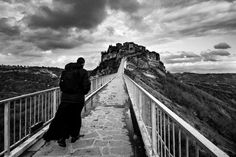 """Civita di Bagnoregio 2008. A priest runs through the bridge that leads to the village of Civita di Bagnoregio. Founded by Etruscans more than 2500 years ago it is called """"the dying city"""" due to erosion. http://ift.tt/2mBfzxo #reportage #blackandwhite #Italy #viterbo #lazio #civitadibagnoregio #heritage #priest #bridge #all_shots #art #beautiful #capture #composition #exposure #focus #instagood #moment #photo #photography #photooftheday #photos #pic #picoftheday #pics #picture #pictures…"""