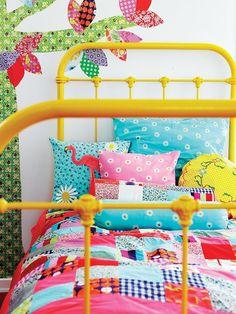 quarto infantil com colcha em patchwork, cama de ferro amarela e adesivo de árvore