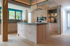 Houten keukens hebben altijd een uniek karakter. Dit project ademt de sfeer van 't strand dankzij vergrijsd eikenhout, ruw beton en een bijzondere afzuigkap