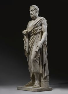 A MARBLE FIGURE OF SOPHOCLES, ROMAN IMPERIAL, 1ST/2ND CENTURY A.D., WITH 18TH CENTURY the head (probably not belonging) after a Greek portrait of Sophocles of the early 4th Century B.C., standing with the weight on his right leg and wearing a himation falling from his left shoulder; the base, feet, forearms, tip of nose, eyebrows, back of head, and various drapery parts restored in marble restorations