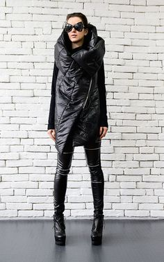 Extravagant sleeveless black coat - METC0040  This large hooded black vest is a great addition to your winter clothing collection. The shape is very modern and it suits numerous under pieces. You can wear it in multiple ways as shown on the pictures.  Pair it with some cool leggings for the ultimate Wow! effect: https://www.etsy.com/listing/256983112/black-leather-tight-pants-extra-long?ref=shop_home_active_2  This sleeveless beauty is made of high quality quilted cotton.  WHEN YOU PLACE AN…