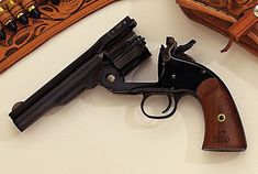"""The Smith & Wesson Schofield wasn't as popular as the Colt back in 1875, but the clone became popular after one was featured in the Clint Eastwood movie """"Unforgiven."""" The gun loads by swinging down the hinged barrel, which activates the ejector rod that, in turn, pops out all six shells at once."""