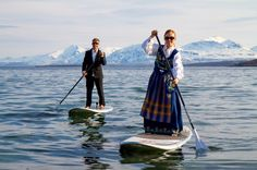 On surfboard in national costume (bunad) from Nordland in Norway