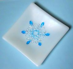 This art glass plate is made of a beautiful white iridescent glass that has a sparkling blue snowflake adorning its center. The opaque white glass has a rainbow iridescent coating so you see hints of many colors sparkling at you when you hold it under the light. The iridescent coating also gives the plate a satiny finish that reminds you of frosty ice so is a perfect resting place for the beautiful snowflake in the center. The snowflake is made of clear and transparent turquoise blue glass.