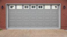 Garage with doors, brick wall and asphalt driveway. Big garage with gray doors, , Craftsman Garage Door, Carriage House Garage Doors, Garage Door Lock, Garage Door Replacement, Modern Garage Doors, Garage Door Opener Remote, Garage Door Springs, Overhead Garage Door, Garage Door Repair