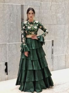 Looking for Beautiful bottle green lehenga with bell sleeved blouse and floral print along with a layered lehenga skirt? Browse of latest bridal photos, lehenga & jewelry designs, decor ideas, etc. Indian Fashion Dresses, Indian Gowns Dresses, Dress Indian Style, Indian Designer Outfits, Indian Designers, Indian Fashion Trends, India Fashion, Fashion Outfits, Lehenga Designs