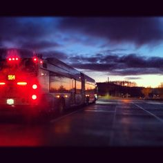 Stormy Sunset.  Sound Transit bus at Issaquah Highlands Park n' Ride in Issaquah WA.  Heavy rain with a sunset in the distance