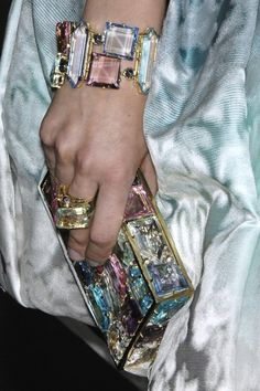 I'd love to know the story behind this bracelet and that clutch. Glass? Real stones? Who designed them? Who sells them?