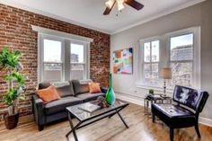 Die Backstein-Mauer fügt Wärme und Textur dieser weißen getrimmte Wohnzimmer.