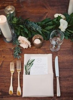 Olive branch place setting on rustic wood tables at a sweet Southern wedding. Green garland table runners and gold flatware. Photo: Cassidy Carson