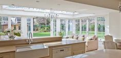 The addition of this conservatory allows light to flood into the kitchen and create a space for relaxing. The conservatory has an inset glazed roof and double doors open ot the garden.