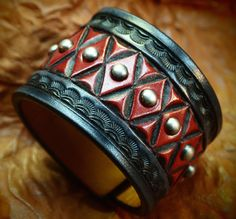 This Black and red hand dyed leather cuff uses natural american veg-tan leather that is lined in smooth calfskin. It is Hand tooled in a unique