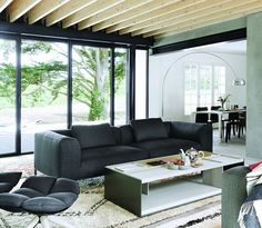 Contemporary living room with charcoal grey couch, large area rug, exposed wood beams, and glass sliding doors