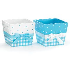Blue and white square planter with polka dots and check pattern. Satin ribbon tied in bow around middle.  Wood