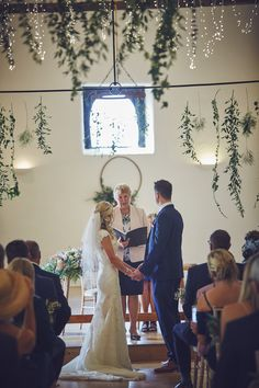 Hanging hoop with partial floral decoration at the back of the barn with hanging curtain of eucalyptus, soft ruscus and ivy with fairy lights. and hanging hoops of foliage. Designed by Darling Buds florist. Barn wedding in the summer.