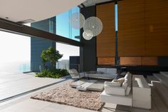 Massive, two story living room blends seamlessly with an elevated, glass wrapped patio through a large sliding panel. Natural wood panels cover the left wall, while full height glass fills the upper patio wall. Modern white leather sofas wrap around a multi-segment coffee table over large beige rug.