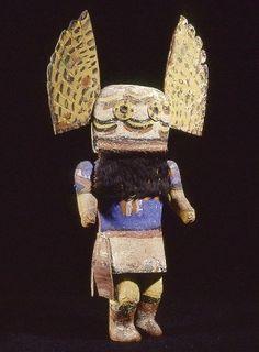 Poupée Kachina Paiyakyamu ou Koyala, Cette poupée, et le masque auquel il se réfère, est généralement considérée comme la mère de tous les autres Kachina.   Représentant Angwusnasomtaka ou Tumas, la Mère-Corbeau, cette poupée Kachina est masquée d'un heaume auquel sont raccordées deux grandes ailes. Les bras, également rapportés, sont articulés, ce qui est fréquent dans les représentations Zuni.