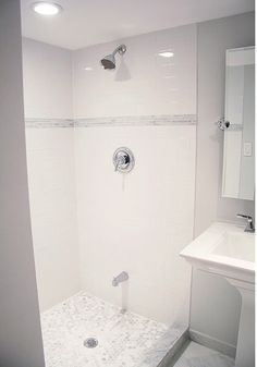 Lovely basement bathroom design with light gray walls paint color, glossy subway tiles backsplash, Moen shower kit, marble hex tiles shower floor, Kohler Memoirs Pedestal Sink, and Delta Dryden Faucet Set.
