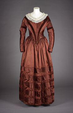 Woman's day dress of deep red silk satin, trimmed with matching red velvet: English, c. 1838 - 1840  Museum reference A.1972.102