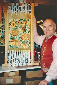 MAISON LESAGE  M. Lesage holding a panel in progress for the jacket designed by Yves Saint Laurent with embroidery executed by MAISON LESAGE.
