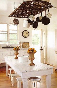 A flea market farm table creates the perfect kitchen island. An old garden gate is repurposed into a rustic pot hanger while an old sideboard, salvaged marble slab and basic soap-stone potting-shed sink create the perfect country-style kitchen sink.