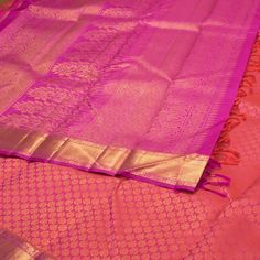 """The """"Sea Pink"""" colour #handwoven Kanjivaram Silk Sari from #Kanakavalli is woven with floral motifs in gold colour zari all over the body that is set off by zari border on either side. The """"Sky Magenta"""" colour pallu is adorned with paisleys motifs in zari. The border is repeated on the """"Sky Magenta"""" blouse that completes the sari."""