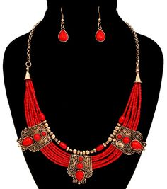 Red Beaded Boho Statement Necklace Multi row of red seed beads with burnished gold components. Gold components with red stones for a tribal look. Bohemian nec