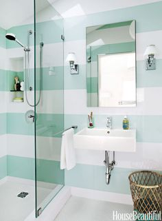 """Designer Angela Free installed tiles to form wide, horizontal stripes in a 37-square-foot guest bathroom in a San Francisco, California house. """"Stripes are a nice, graphic design element that can bring movement and pattern to a room, but not in a busy way,"""" she says. By wrapping the pattern around the space, she opened it up and created """"flow, a borderless space."""""""