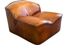 "A 1970s low-slung English leather lounge chair by the famed New York maker, Pace Collection. The leather is a natural golden brown similar to an aged baseball mitt. Great lines and beautiful design details. Excellent condition. Seat, 14""H x 23""D."