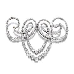 A diamond and platinum brooch designed as a collet-set old European-cut diamond scroll; estimated total diamond weight: 12 carats.