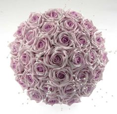 An all lilac rose bridal bouquet finished with ivory pearl strands.  The stem is bound in ivory satin ribbon and bow.    Measurements  Width- 9 inches  Length- 8 inches
