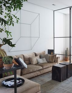 In the main living area of Frank Nederhof's renovated Amsterdam flat, a geometric sculpture by Antonino Sciortino hangs above an Erik Kuster sofa. The coffee tables are made from fossilized wood so heavy that each one requires two people to lift it.