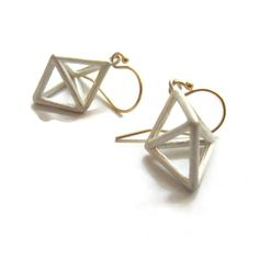 Part of my crystal series, I deconstructed cut gemstone shapes . Double pyramids.  I have paired the  silver with 14K solid gold wires for a nice contrast. They are open and light have nice presence the ear.Size: Inclusive of ear wire they hang down 1.15 inches 29mm the silver pyramid shape is 17 x 12 mm .7 x .45 inches.
