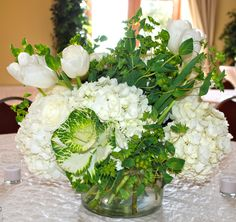 centerpieces of white hydrangea, bupleurum, kale, white tulips and roses.