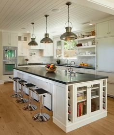 Beautiful kitchen with tongue and groove ceiling illuminated by three hammered metal pendants hung above the large kitchen island with prep sink framed by a sleek black counter lined with black Piston Barstools with glass front cabinets on each end flanked by wine racks on either side.