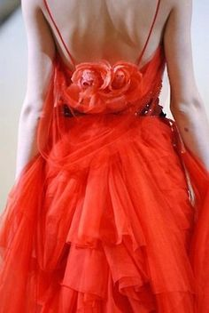 Orange chiffon ruffled dress. Look at the two roses in the back.   Recreate the look:  http://www.ebay.com/itm/Alythea-Gorgeous-Tiered-Ruffles-Sleeveless-Asymmetrical-Coral-Tunic-Dress-M-/380997867653?pt=US_CSA_WC_Shirts_Tops&hash=item58b53e1885