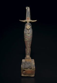 The inscription identifies this figure as Osiris. He wears the crown of ostrich feathers, a sun-disk, and the ram's horns that identify him as a king. Yet he is also in the form of a mummy with the curled beard worn by the dead.