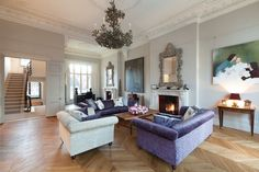gray and purple living room with chevron floors, an ornate mirror & fireplace