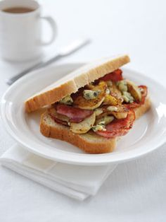 Build a Better Buttie  Here in England the buttie is a bacon sandwich…greasy, buttery, bacony and delicious. It is also know to be a hangover cure…Here is a recipe for a bacon buttie…this one with English bramley apples and stilton cheese…put it in or leave it out…have a buttie!  6 rashers of bacon, back bacon or thick slices  1 bramley apple cored and sliced (optional)  4 slices of thick bread or a roll  butter  stilton or blue cheese (optional)  Cook baco
