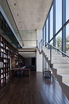 Biblioteca de doble piso con pequeño escritorio en espacio de escaleras